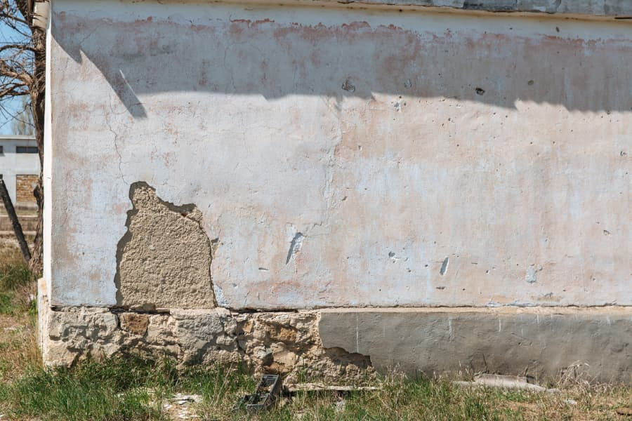 foundation of a building slowly sinking, causing a cracked, broken wall